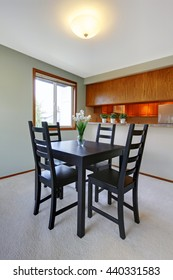 House interior. Simple black table set and one window in small dining room with view of the kitchen.