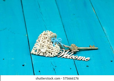 House key attached to natural wicker heart with ribbon and Welcome on antique rustic teal blue wood background; new home, Valentines Day, love and welcome home  background with painted copy space