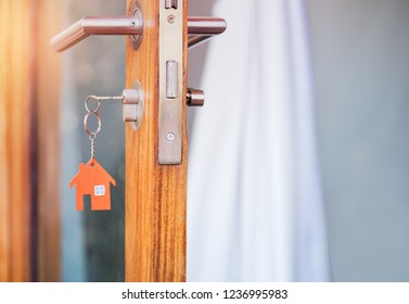 House key in the door with with house shaped keychain.