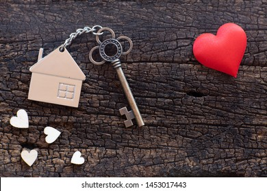 House key in heart shape with home keyring on old wood background decorated with mini heart, home sweet home concept, copy space