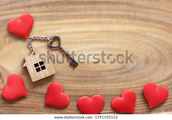 House key in heart shape with home keyring on wood background decorated with mini hearts, copy space
