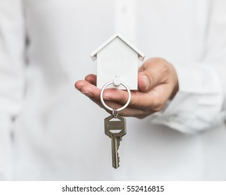 House key in home insurance broker agent's hand protection or in salesman person giving to buyer customer
