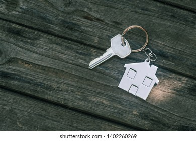 House key with home keyring in on old wood background, copy space