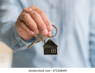 House key lock in real estate sale person, landlord or home Insurance broker agent's hand giving to buyer customer for new family property ownership guarantee and safety assurance concept