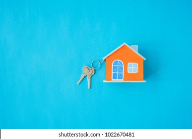 House and key on blue background. Minimal creative style.