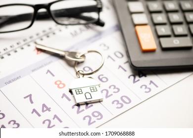A house key on a calendar background close up