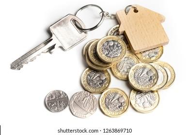 House key on key chain with UK money, property market, sale, or rental