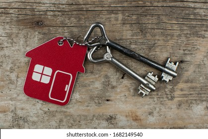 House key on a house shaped keychain resting on wooden floor boards concept for real estate, moving home or renting property