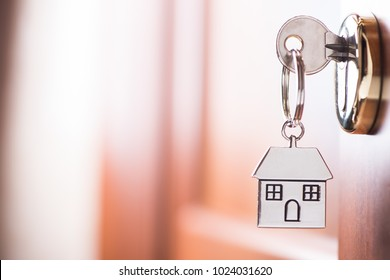 House key on a house shaped silver keyring in the lock of a entrance  brown door