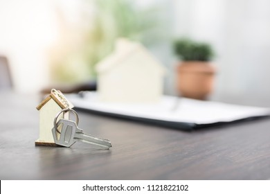 house key on table with contract form, selling and buying home or condo concept