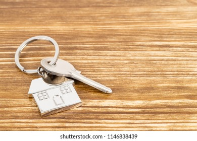 House key on wooden background concept for mortgage