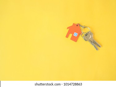 House and key on yellow background. Minimal creative style.