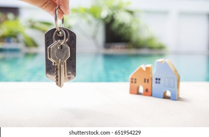 House key over blurred miniature house on swimming pool edge, property and real estate business concept, outdoor day light
