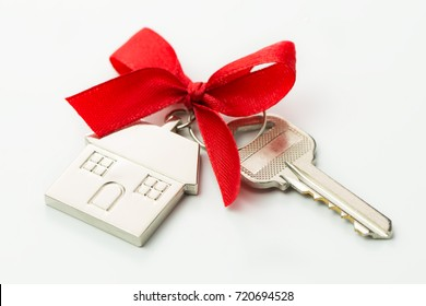 House key with red bow over white background