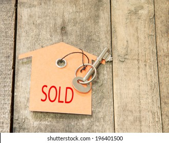 House Key with Sold tag  on a background of wooden.