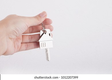House key with trinket house in the female palm. Rental estate. Sale property template.