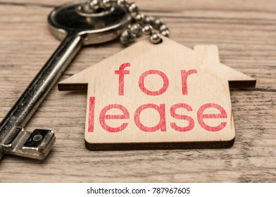 House key with wooden house key chain writing for lease