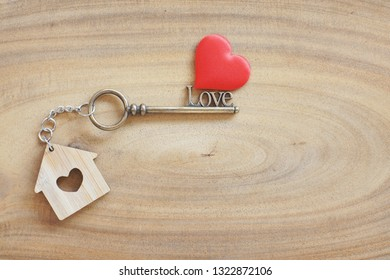House keyring and love shape key on vintage wooden table. Decorated with mini heart as sweet gift for lover or family member. Home sweet home concept. Copy space.