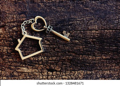House keyring with vintage heart shape on old wooden table. Welcome new home, home sweet home concept. Copy space.
