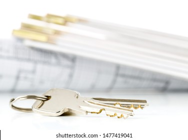 House keys in front of house architectural blueprint and folding rule over white background with selective focus - home owner, real estate or house building concept