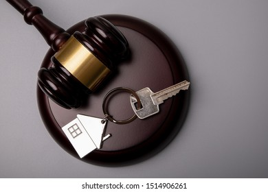 House keys and judge's gavel on a gray background. Mortgage, bankruptcy or divorce concept