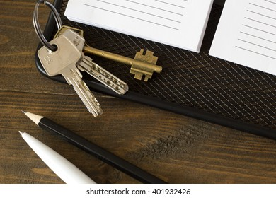 house keys on a notebook and a pen , pencil top view