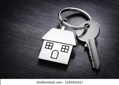 House keys on a house shaped keychain resting on wood background concept for real estate, moving home or renting property