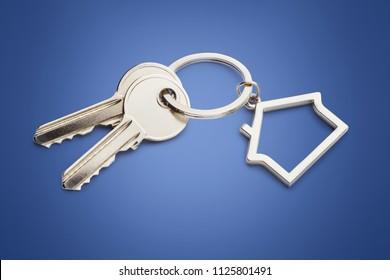 House keys with house shaped keychain,  on blue background