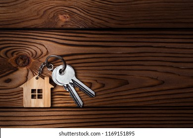 House keys with house shaped keychain on wooden background, view from above