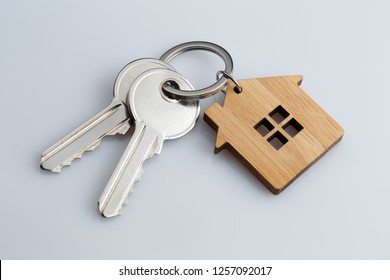 House keys with house shaped keychain on grey background