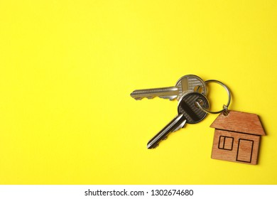 House keys with trinket on color background, top view. Space for text