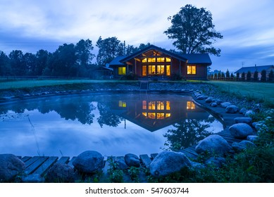 House at the lake, reflected on water, in twilight