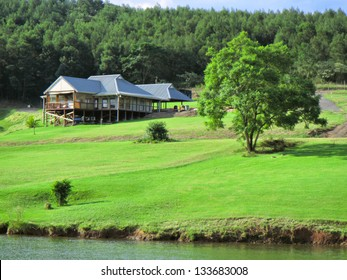 House with lawn on lake shore. Shot in Albert Falls Dam Nature Reserve, Kwazulu-Natal, South Africa