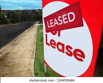 House for lease sign in front of a home with the leased sticker