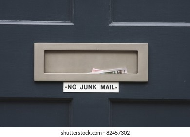 House letterbox with 'No junk mail' sign and junk mail