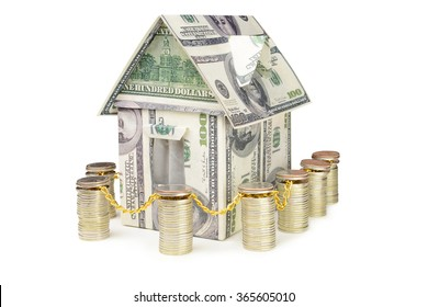 House made of money surrounded by a fence from coins, on a white background