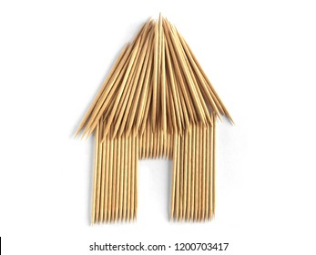 House made of toothpicks isolated in white background. Many toothpicks shaped as a creative hut for home concept.