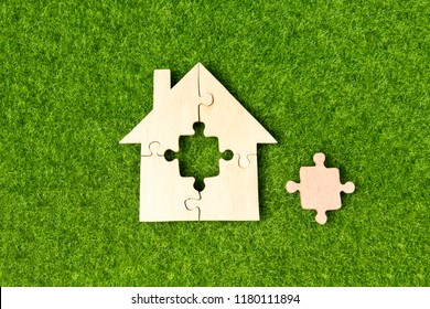 house made of wooden puzzles against a background of green artificial grass. logic, business planning, education.