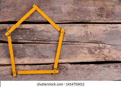 House made from yellow folding ruler. Yellow folding ruler in a shape of house. Space for text. Home renovation concept.