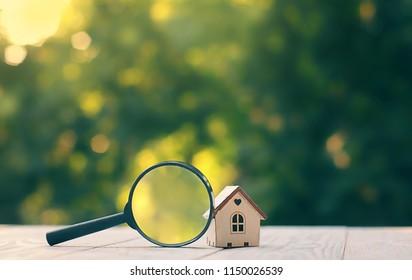 Einzel- und Vergrößerungsglas. Haussuche Konzept, Wahl des Ortes für den Bau, Hypotheken, Mietwohnungen. Haus in der Natur, Sommersaison. Bau, Verkauf, Leasing.