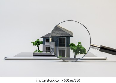 house miniature model on tablet pc and magnifying glass, searching or checking concept