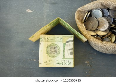 House mock up from Saudi Riyal on wooden table. Real estate and business concept.  Top shot with bag of coin