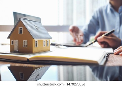 House model and business Insurance authorities showing an insurance policy and dealing the policyholder must to sign.