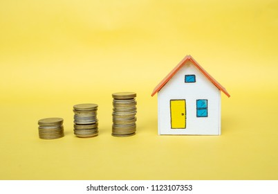 House model and coin money on yellow background,finance and banking concept,Minimal creative style.