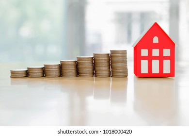 House model and coin money,mortgage and real estate investment.