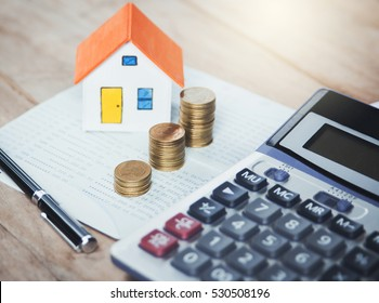 House model and coin on Bank account ,calculator on table for finance ,banking concept.
