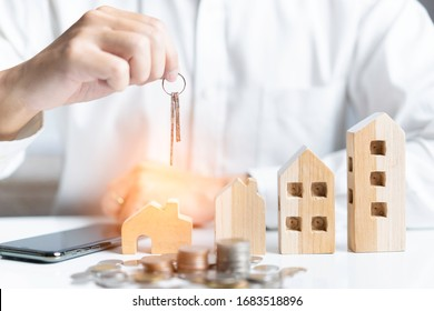 House model and Coins stack. Key of home on hand of bank employee to sell  house after approve loan and. Concept of property mortgage and investment for a house.