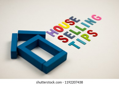 House model and colorful wooden alphabet with text house selling tips. Property and mortgage concept