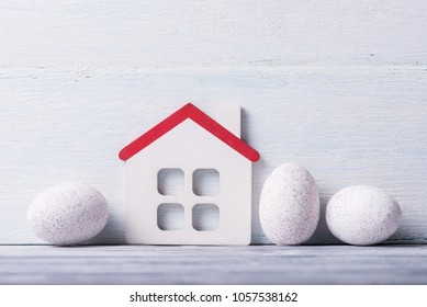 House model with Easter eggs over white wooden background.