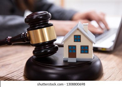 House Model With Gavel In Front Of A Businessperson Using Laptop On Wooden Desk